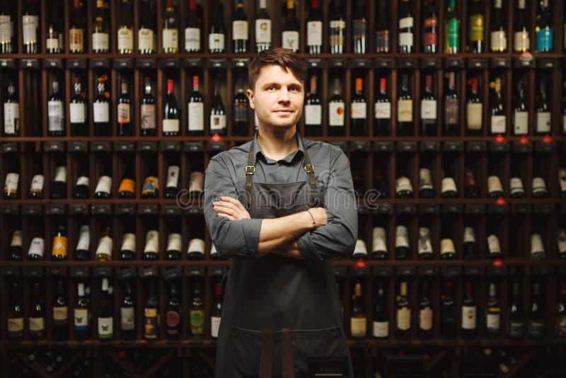 Le Barkeeper se tient dans la cave avec des étagères pleines des bouteilles photo libre de droits