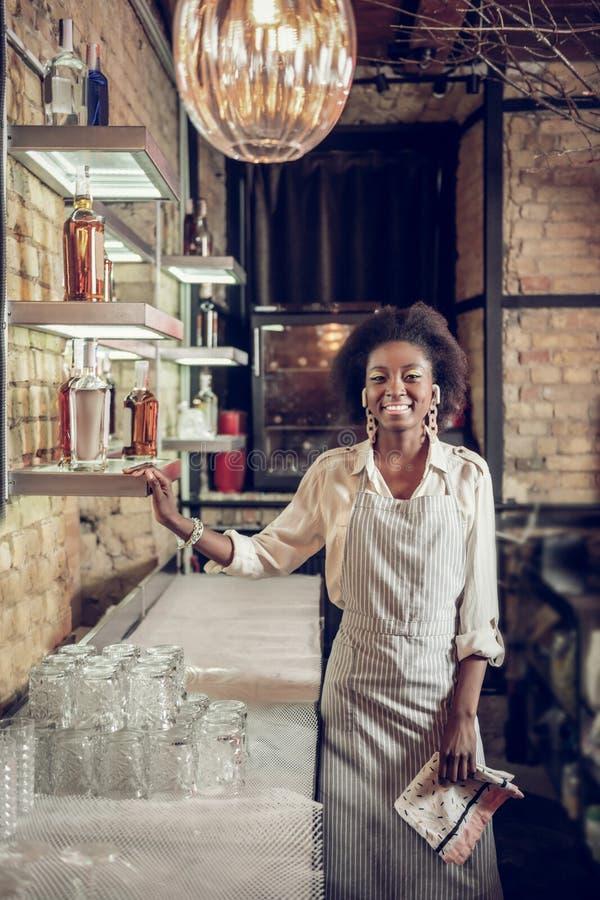 Le barman afro-américain de lancement se tenant sur des étagères de barre a rempli alcool photos libres de droits