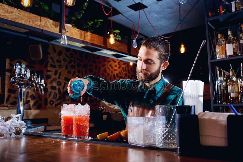 Le barman avec une barbe fait le cocktail à la barre photographie stock