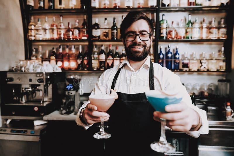 Le barman avec une barbe a préparé un cocktail à la barre photo libre de droits