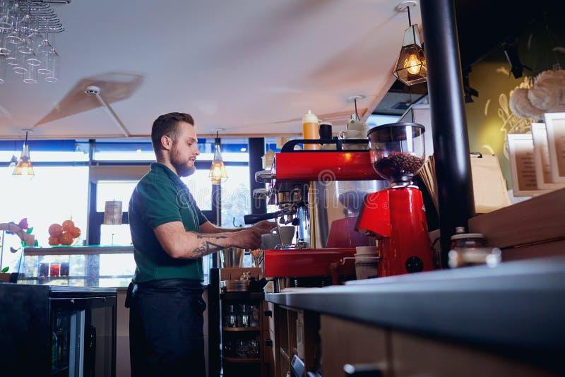 Le barman, barman, fait un café chaud boire au compteur de barre dedans photos libres de droits