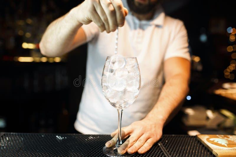 Le barman dans le T-shirt blanc à la barre ou dans une boîte de nuit et fait un cocktail alcoolique lifestyle photographie stock