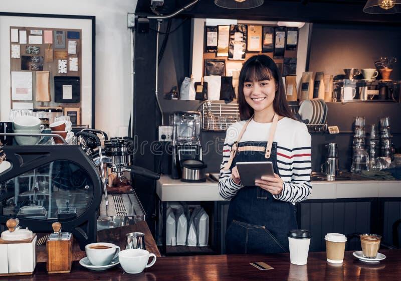 Le barman de femme prennent l'ordre avec le comprimé, utilisation femelle de serveuse de l'Asie photos stock