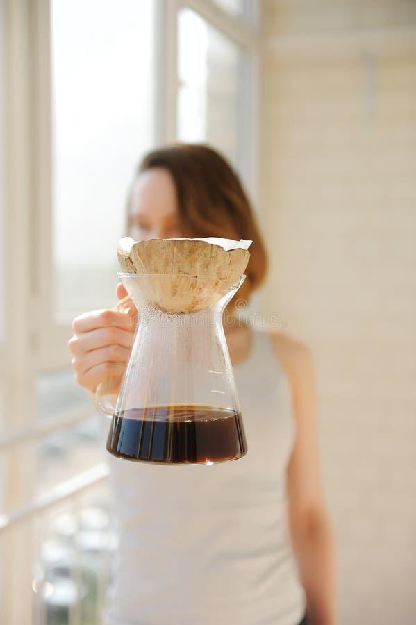 Le barman de fille tient un brassage alternatif de café de noix de coco de coquille d'égouttement créatif peu commun de pourover photographie stock