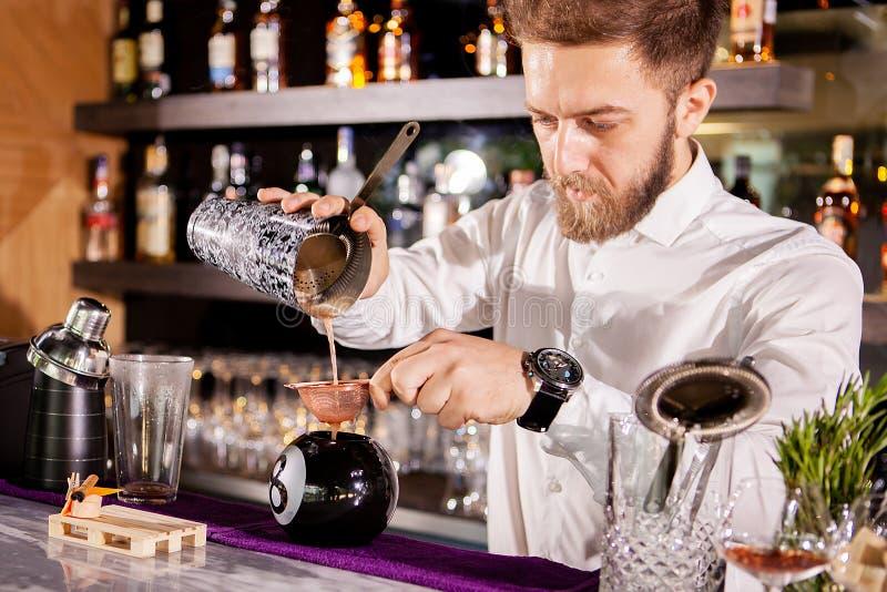 Le barman de barman verse une boisson image libre de droits