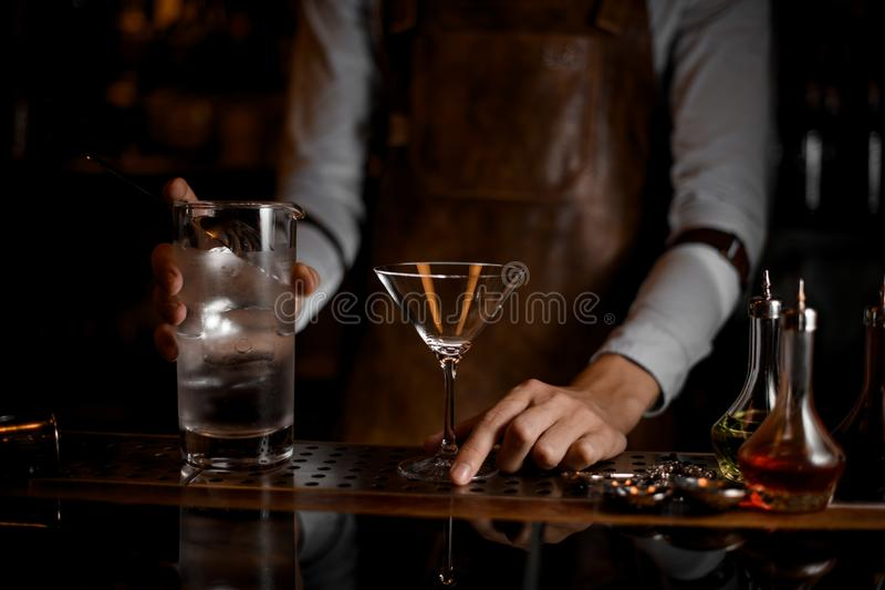 Le barman dispose à verser un cocktail de martini photo libre de droits