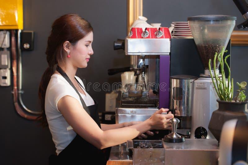 Le barman féminin fait le café utilisant la machine de café photographie stock