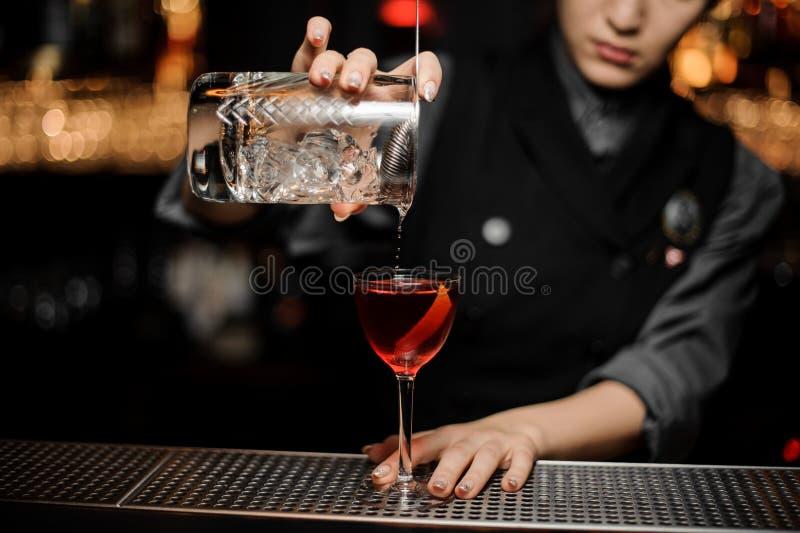 Le barman fait le cocktail utilisant le verre avec le tamis photo stock