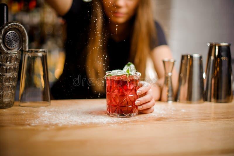 Le barman finit la préparation du cocktail alcoolique rose en ajoutant un amer du sucre en poudre photo stock