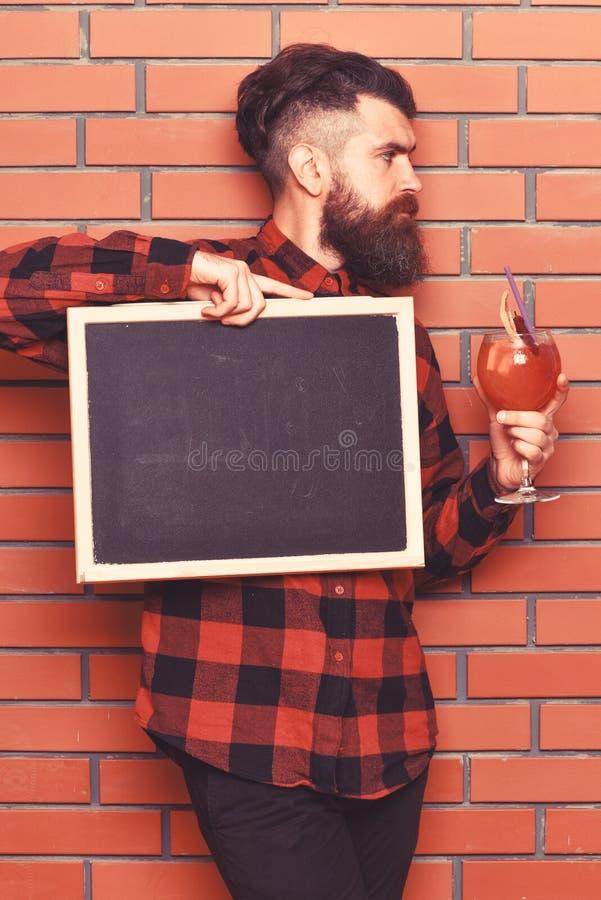 Le barman, hippie tient le cocktail et la publicité L'homme tient le verre images libres de droits