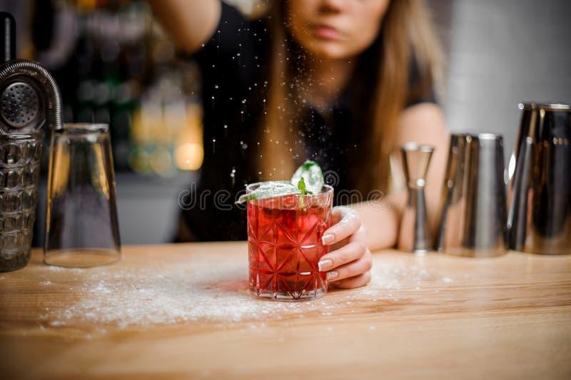 Le barman mignon finit la préparation du cocktail alcoolique avec les feuilles en bon état du sucre en poudre photographie stock
