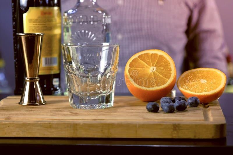 Le barman prépare les ingrédients pour le cocktail d'alcool avec la tequila, l'angustura amer et les fruits Remet le plan rapproc image libre de droits