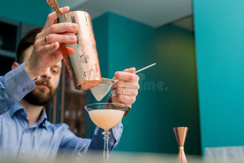 Le barman prépare un cocktail images stock