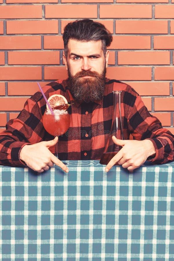 Le barman recommande d'essayer la boisson Barman avec la barbe sur le visage strict se dirigeant vers le bas avec l'index Homme d photo libre de droits