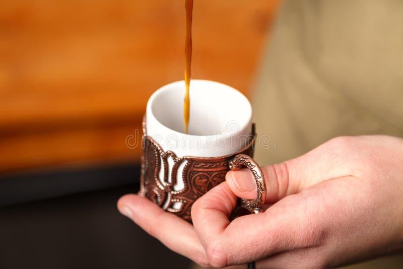 Le barman verse le café turc dans une tasse de relief traditionnelle d'en cuivre en métal, foyer en gros plan et sélectif images libres de droits