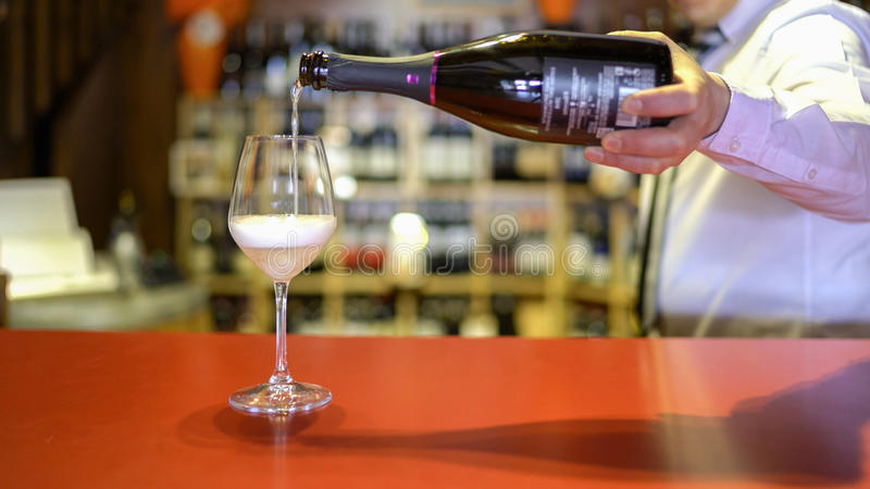 Le barman verse le vin pétillant dans un verre images libres de droits