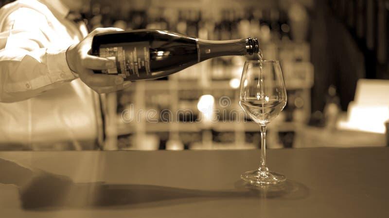 Le barman verse le vin pétillant dans un verre photos libres de droits