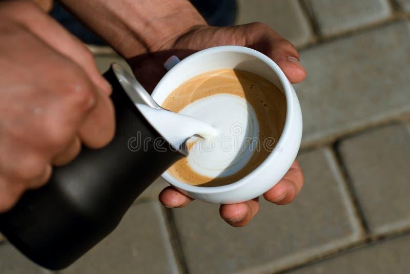 le barman versent le lait dans la boisson de café Passant le grand temps à la maison Détendez en café ou café et boire parfait photos libres de droits