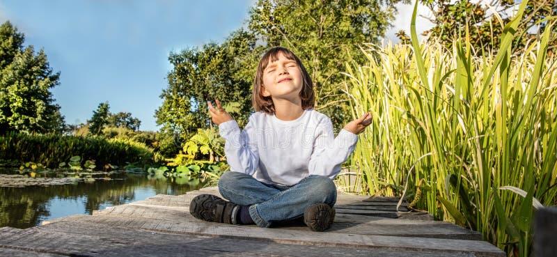 Le barn 5 år gammalt yogabarn i lotusblommaposition royaltyfri fotografi
