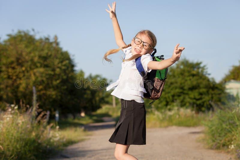 Le barn skola flickan i en banhoppning för skolalikformig på roaen royaltyfria bilder