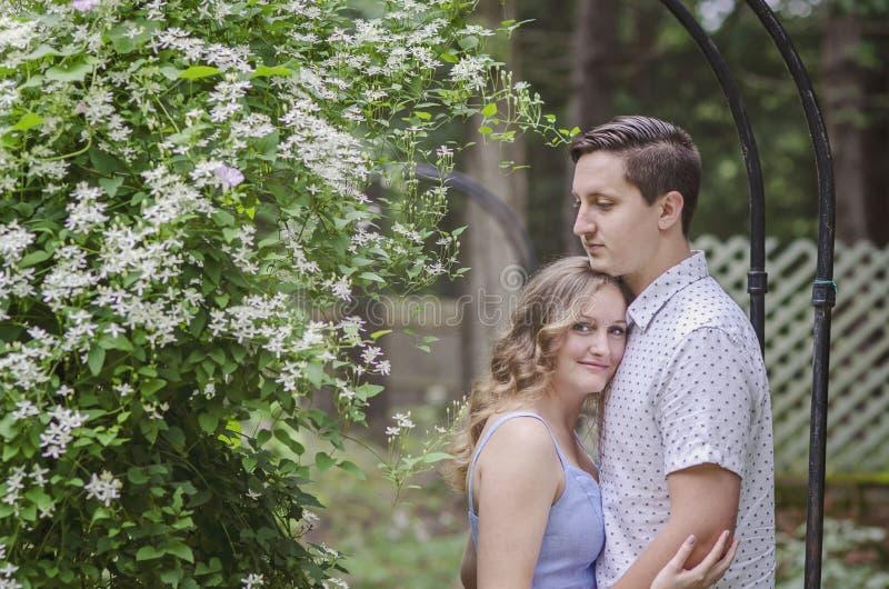 Le barnpar som kramar under blommabåge royaltyfria foton