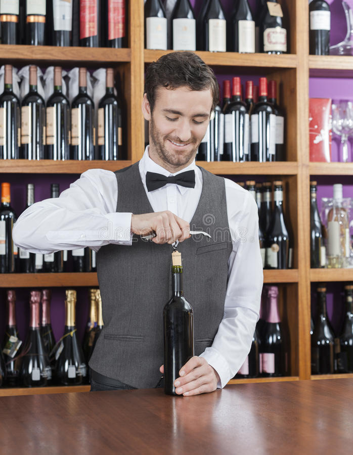 Le bartendern Opening Wine Bottle royaltyfria foton