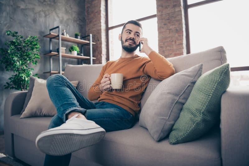 Le bas au-dessous du portrait de vue d'angle à lui il gentil type barbu gai gai attirant s'asseyant sur le latte potable de divan photo libre de droits