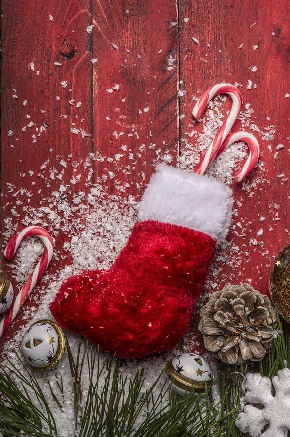 Le bas de Noël avec le pin s'embranche avec les cônes, canne de sucrerie, sur une fin en bois rouge de fond  photo stock