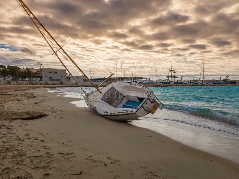 Le bateau à voile a jeté sur le rivage déchiré de la tempête d'amarrages images libres de droits
