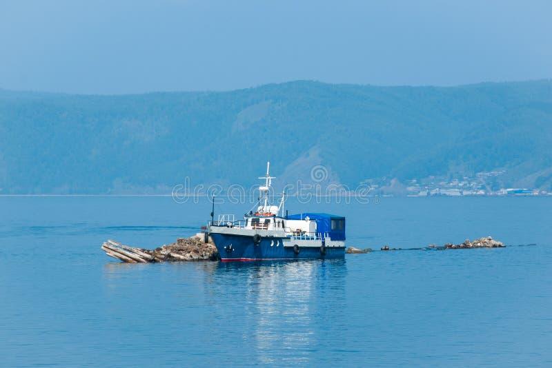 Le bateau bleu ancré sur le lac Baïkal photographie stock libre de droits
