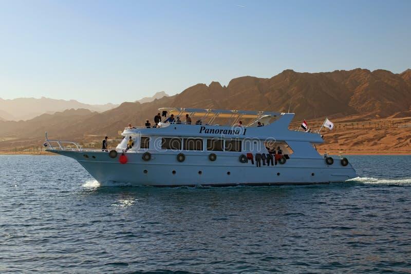 Le bateau de croisière blanc avec des touristes va au récif où les gens plongeront avec la plongée à l'air ou naviguer au schnorc photo stock