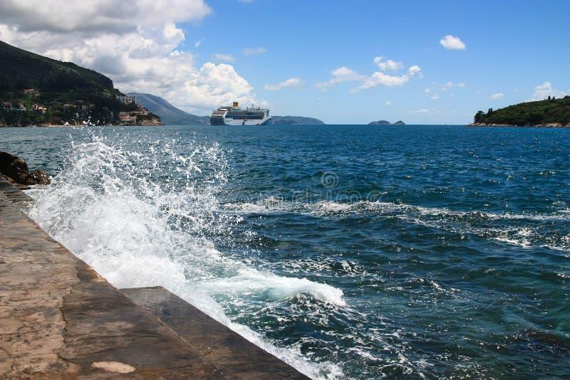 Le bateau de croisière de luxe naviguant pour mettre en communication avec surfer ondule photographie stock