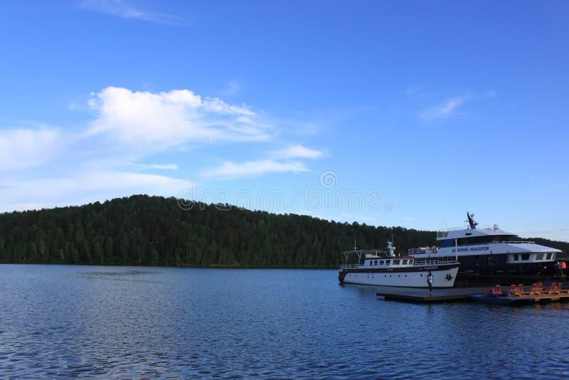 Le bateau de croisière est dans l'eau et il y a des forêts dans la distance photo libre de droits