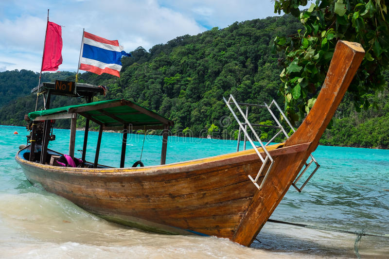 Le bateau de Longtail du stationnement de pêcheur sur la plage de sable ont la mer et le MOIS images stock