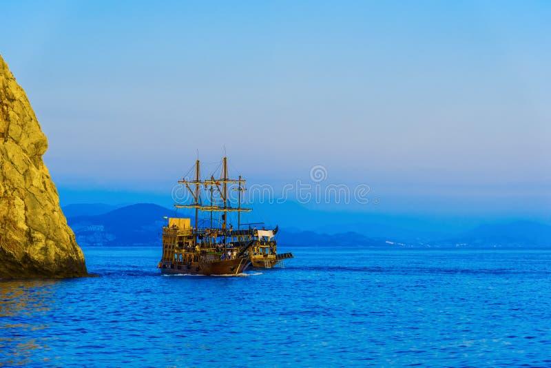 Le bateau de navigation avec des touristes s'approchent de la roche photo stock