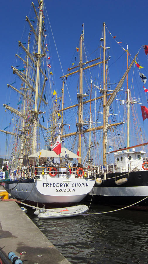 Le bateau de navigation avec les voiles abaissées s'est accouplé dans le port. photographie stock
