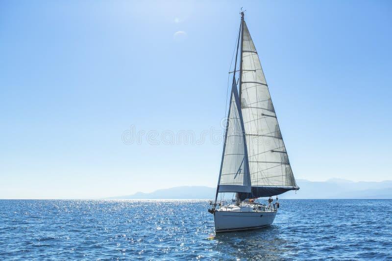 Le bateau de navigation fait de la navigation de plaisance avec les voiles blanches en mer ouverte photos libres de droits
