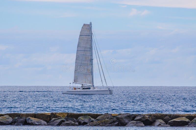 Le bateau de navigation fait de la navigation de plaisance avec les voiles blanches en mer ouverte Boa de luxe images libres de droits