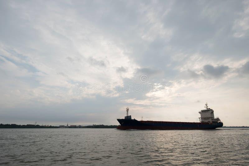 Le bateau de pétrole et de gaz de silhouette montent à travers la rivière avec le ciel de coucher du soleil comme fond image libre de droits