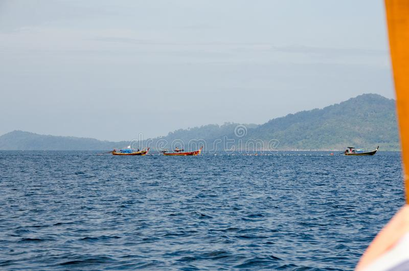 Le bateau de pêche en bois avec la mer verte et le ciel bleu au lever de soleil aboient photos stock