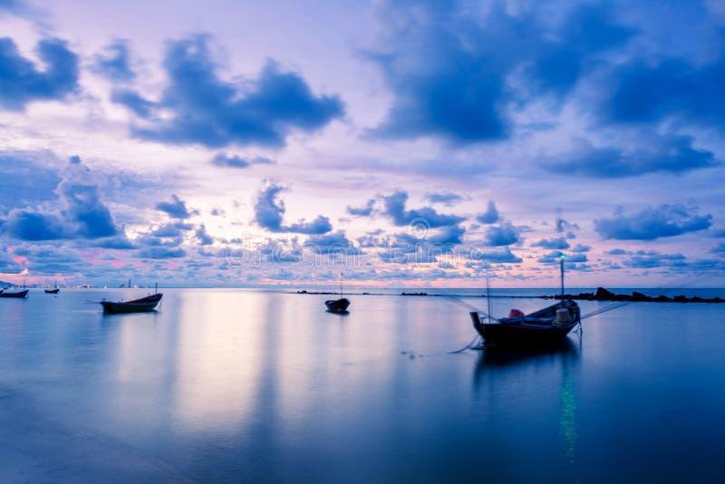 Le bateau de pêche en eau de mer parfaitement calme aiment le verre avec les nuages dans le ciel, longue exposition prise pendant photo libre de droits