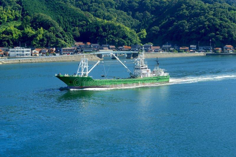 Le bateau de pêche revient au port photo stock