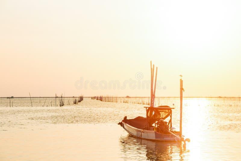 Le bateau de pêche sur l'eau et le soleil de mer est fond photo stock