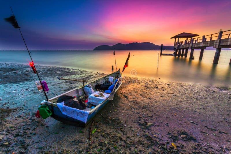 Le bateau de pêcheur garé pendant le coucher du soleil photos stock