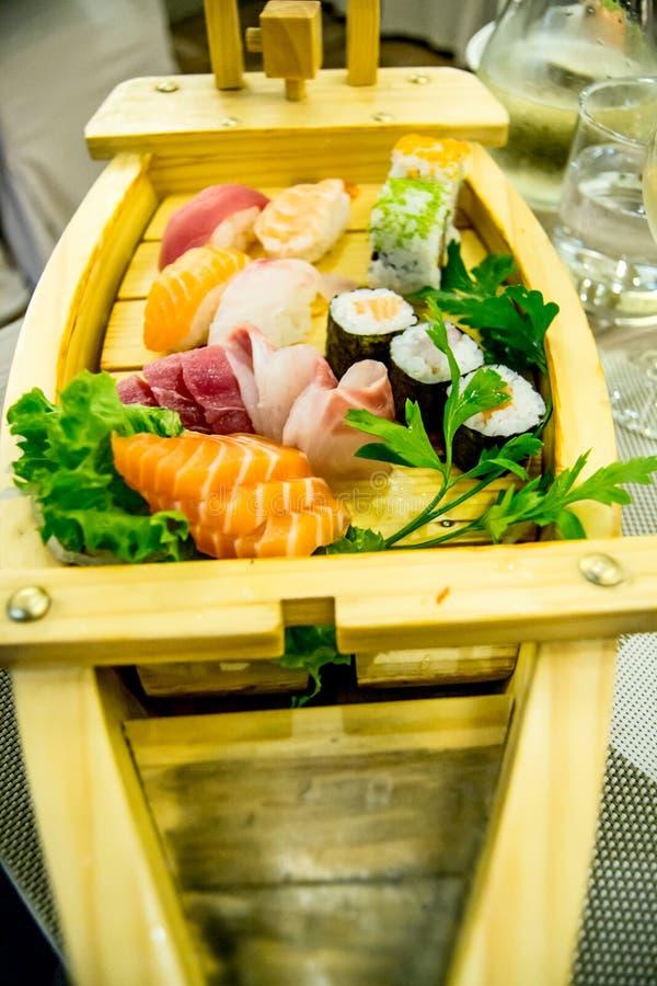 Le bateau de sushi avec différents types de sushi rapièce dans restaurant chinois/japonais images libres de droits
