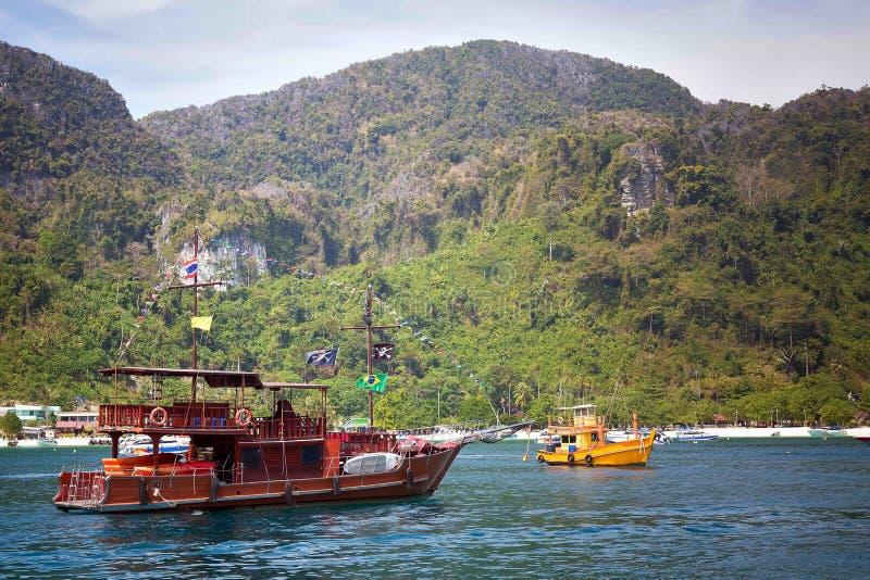 Le bateau de touristes de plaisir moderne, a stylisé comme bateau de pirate Dans la perspective d'un rivage rocheux et d'une plag images stock