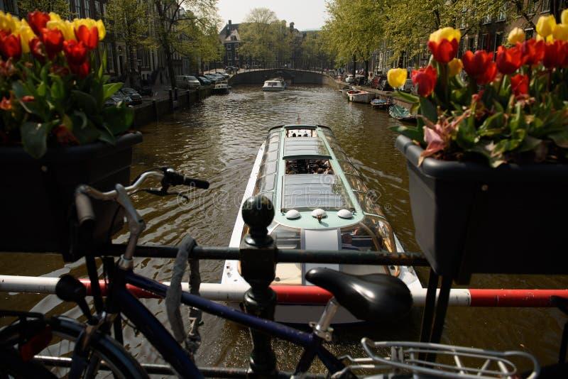 Le bateau de touristes voyage en bas d'un canal à Amsterdam image stock