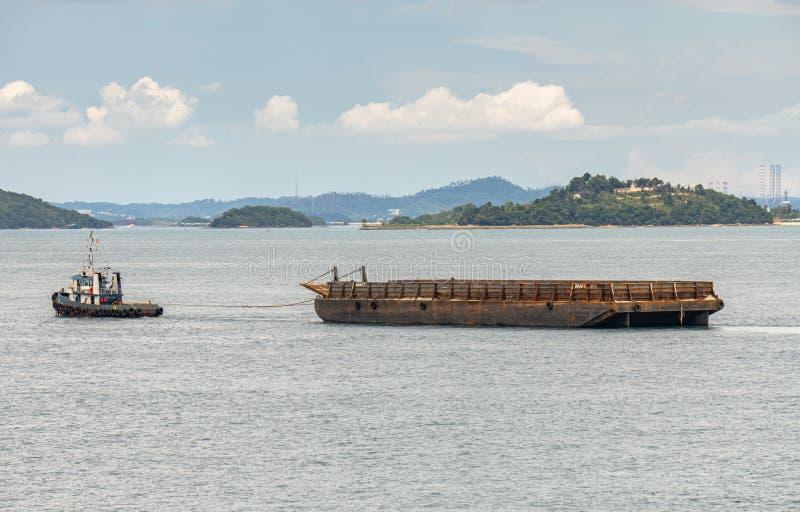 Le bateau de traction subite remorque une péniche plus légère de cargaison en vrac le long de détroit de Singapour près du rivage images stock