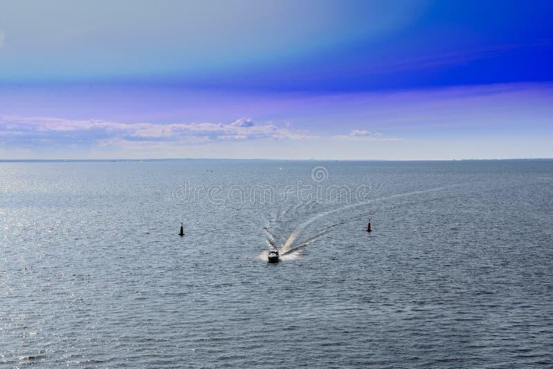 Le bateau des sauveteurs se précipite contre le ciel bleu et la mer sur le fairway photographie stock libre de droits