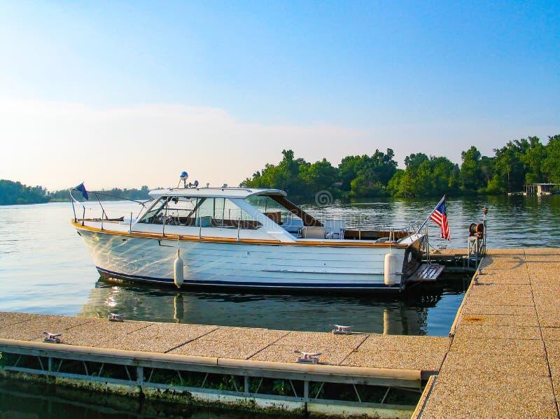 Le bateau en bois de skiff de mer de vintage avec un drapeau américain sur le dos a amarré à un dock dans un lac avec la réflexio photo libre de droits